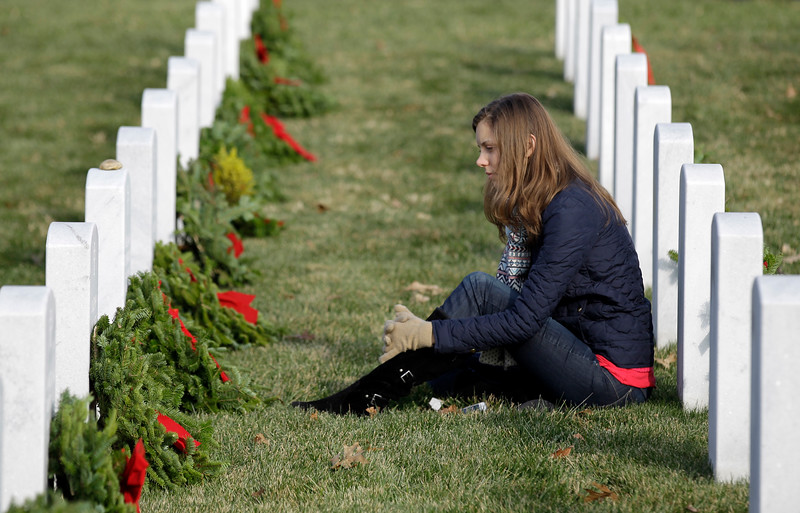 Lianna Bennett sits at the headstone of her grandfather U.S. Army Col. William W. Etchemendy during Wreaths Across America's 150th anniversary, Saturday, Dec. 13, 2014, at Arlington National Cemetery in Arlington, Va. (AP Photo/Luis M. Alvarez)